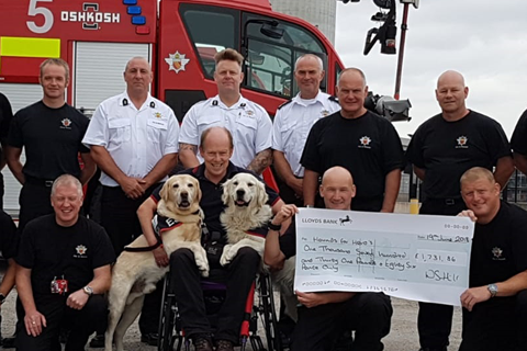 Allen Parton and his two assistance dogs are presented with a large cheque by a group of Fire Service personnel.